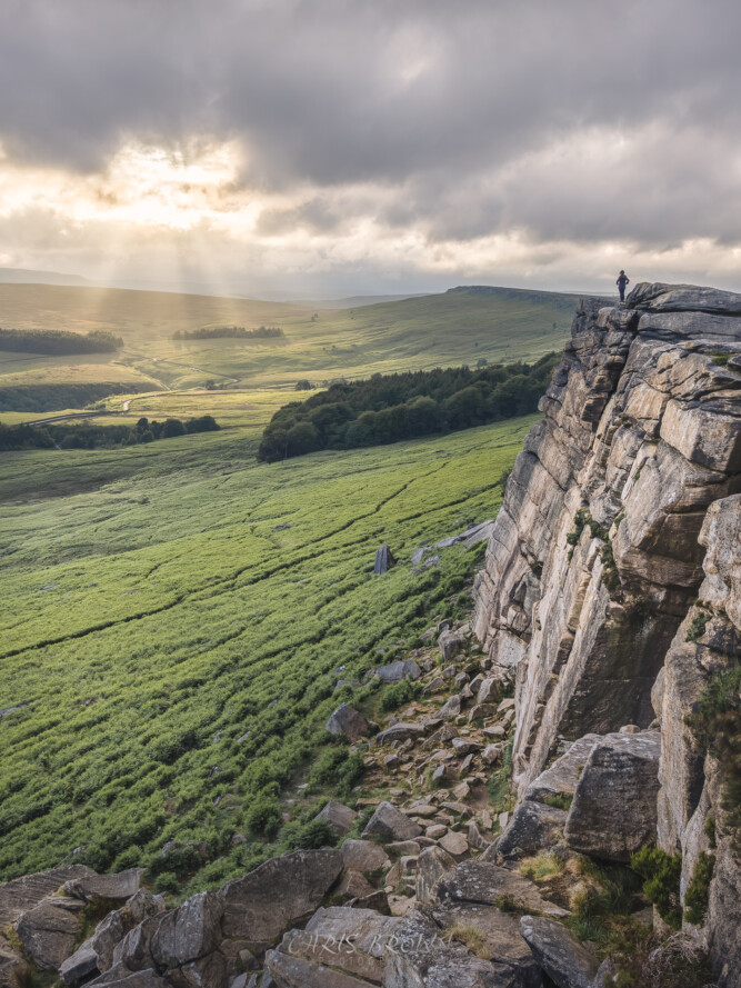 landscape image of Stanage edge sunset across the cliff face